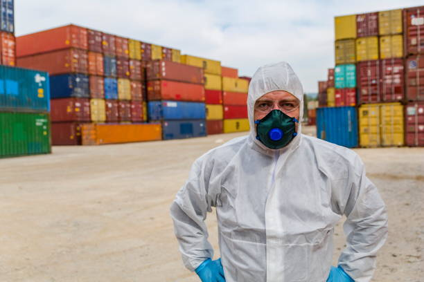 worker in protective suit and containers box from cargo freight ship for import export - essential workers stock pictures, royalty-free photos & images
