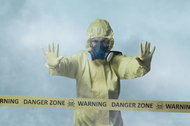 Worker in protective suit showing stop gesture stock photo