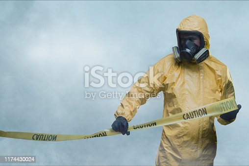 Worker wearing yellow protective suit holding warning tape