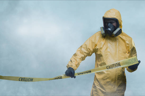 Worker in protective suit with cordon tape stock photo