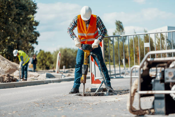 Worker in reflective vest with drill repairing street during roadworks Worker in reflective vest with drill repairing street during roadworks drill stock pictures, royalty-free photos & images