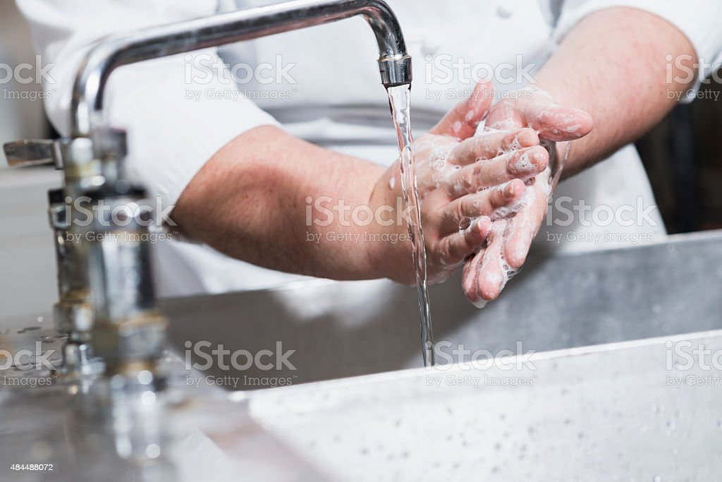Worker in restaurant washing hands in kitchen sink stock photo