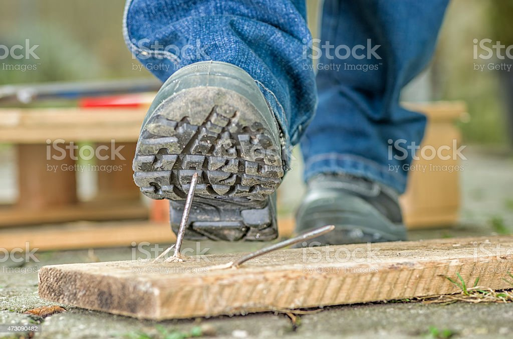Worker in safety boots about to step on a nail stock photo