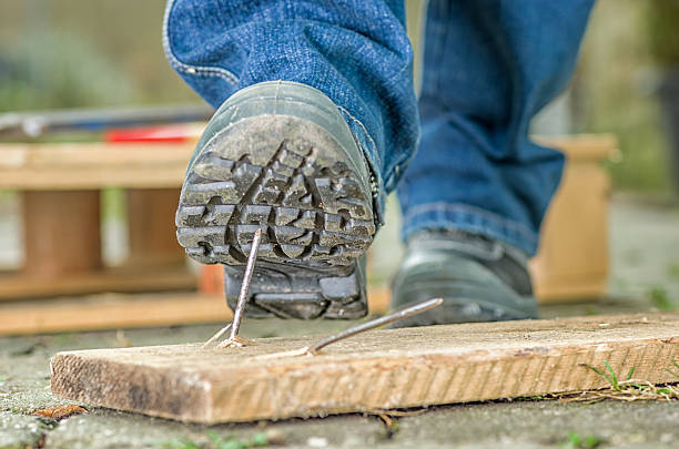 Worker in safety boots about to step on a nail Worker with safety boots steps on a nail stepping stock pictures, royalty-free photos & images