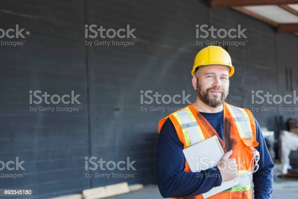 Worker in safety vest and hardhat holding digital tablet picture id693345180?b=1&k=6&m=693345180&s=612x612&h=xhr11 9dlyyybhayuhf4t25vm gz7ibzxlo3v8qt97c=