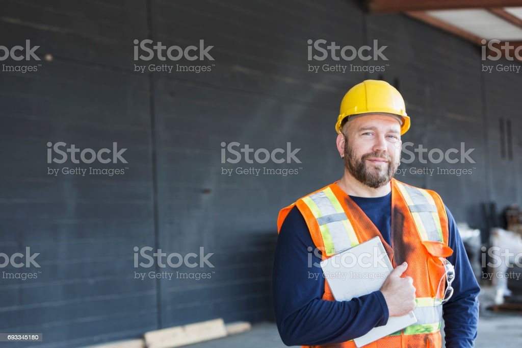 Worker in safety vest and hardhat holding digital tablet stock photo