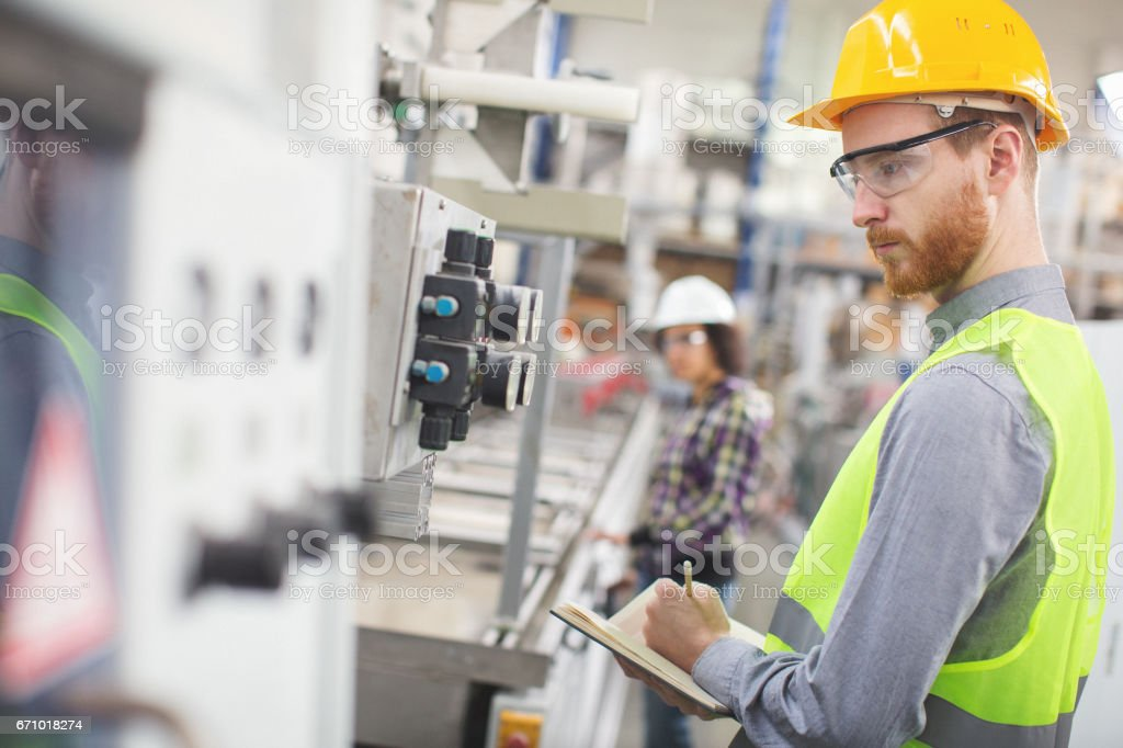 Worker in the factory taking readings stock photo