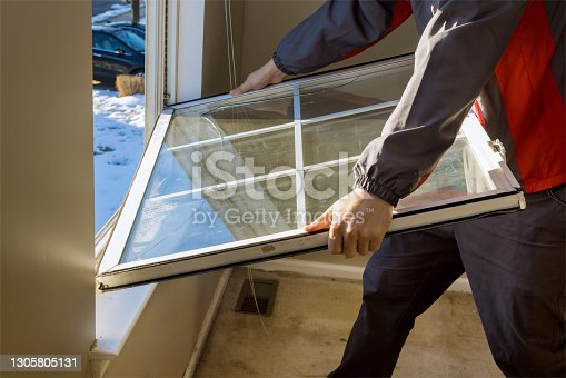 istock Worker in the removing break down, windows in the home renovation living energy efficiency 1305805131