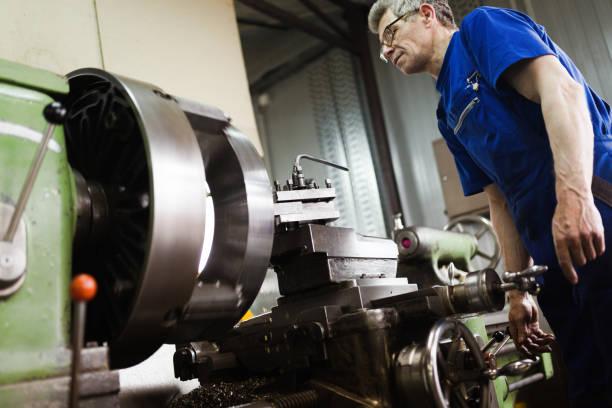 Travailleur en uniforme de fonctionnement en manuel tour dans l'usine de métallurgie - Photo