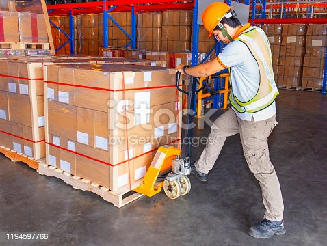 Worker in uniform working with hand pallet truck and cargo pallets shipment at warehouse