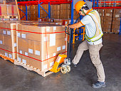 istock Worker in uniform working with hand pallet truck and cargo pallets shipment at warehouse 1194597766