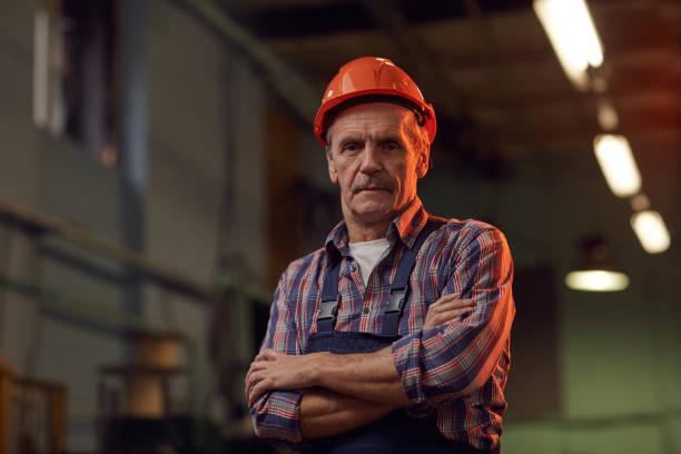 worker in work helmet in the plant - pensionati lavoratori foto e immagini stock