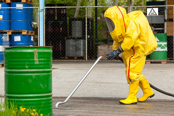 worker in yellow hazmat suit cleaning ground - white suit stock photos and pictures