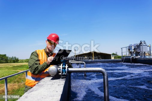 Worker inspecting valve for filtering water. Focus on Valve. Copy space available.