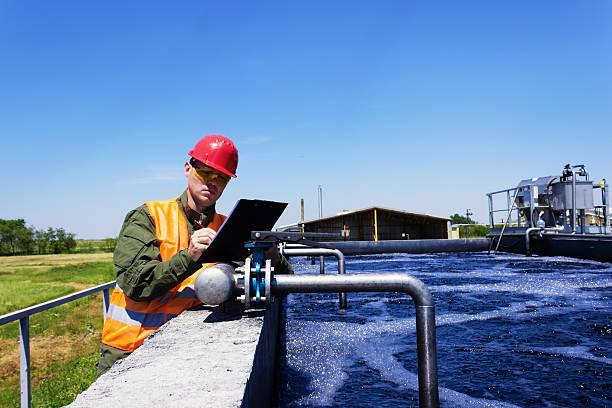 worker inspecting valve - gölet stok fotoğraflar ve resimler