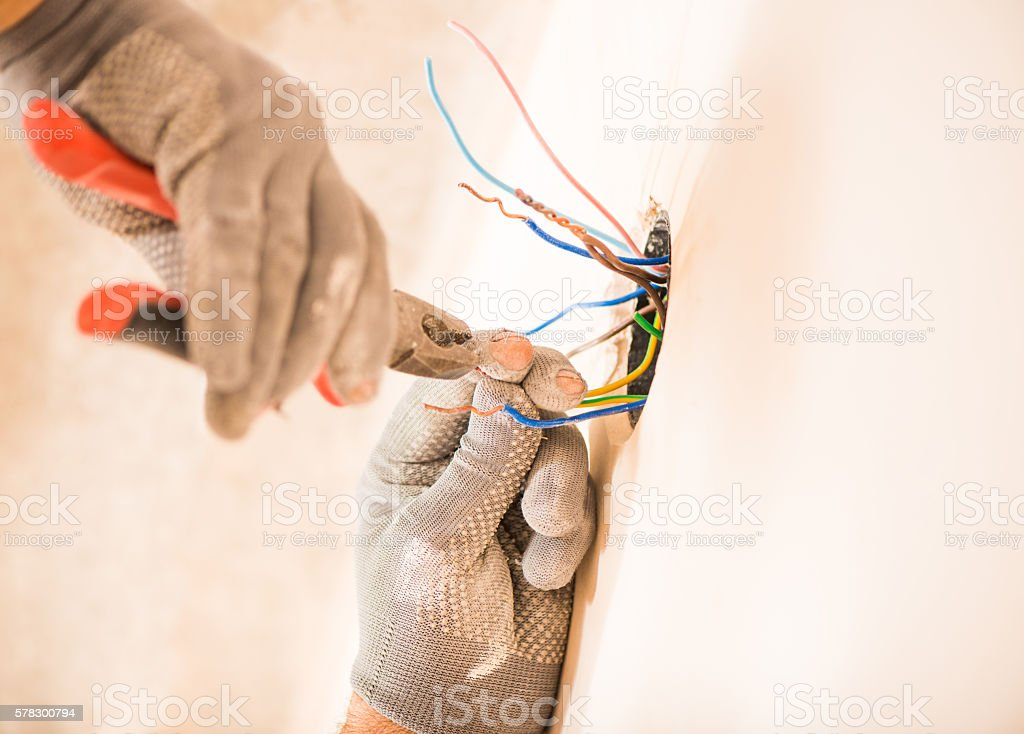 worker instaling electrical wires stock photo