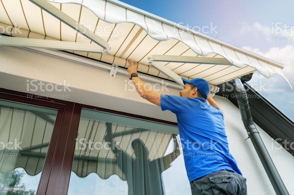 worker install an awning on the house wall over the terrace window stock photo