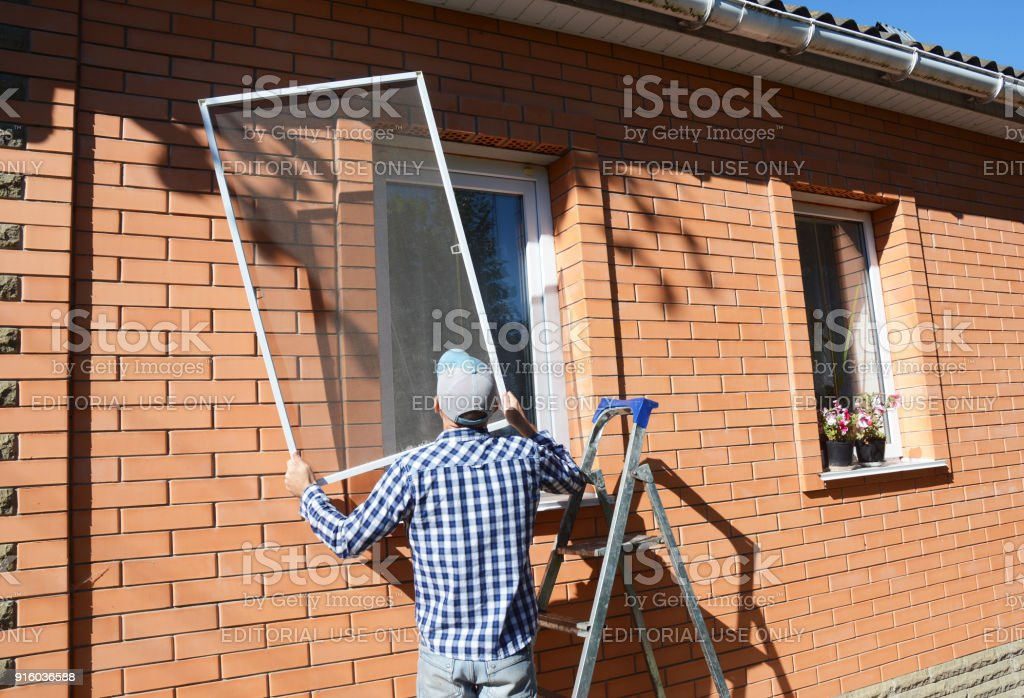 Worker install mosquito net or mosquito wire screen on brick house window. stock photo