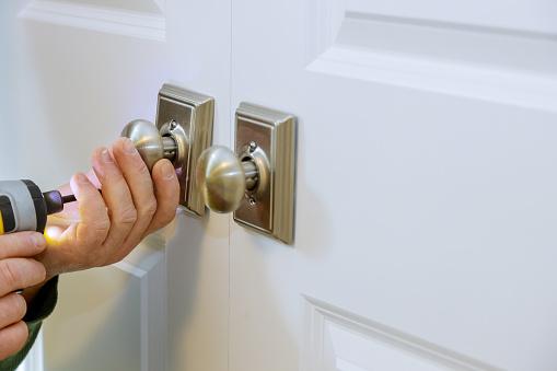 Locksmith worker installing a new dummy lock in house on door
