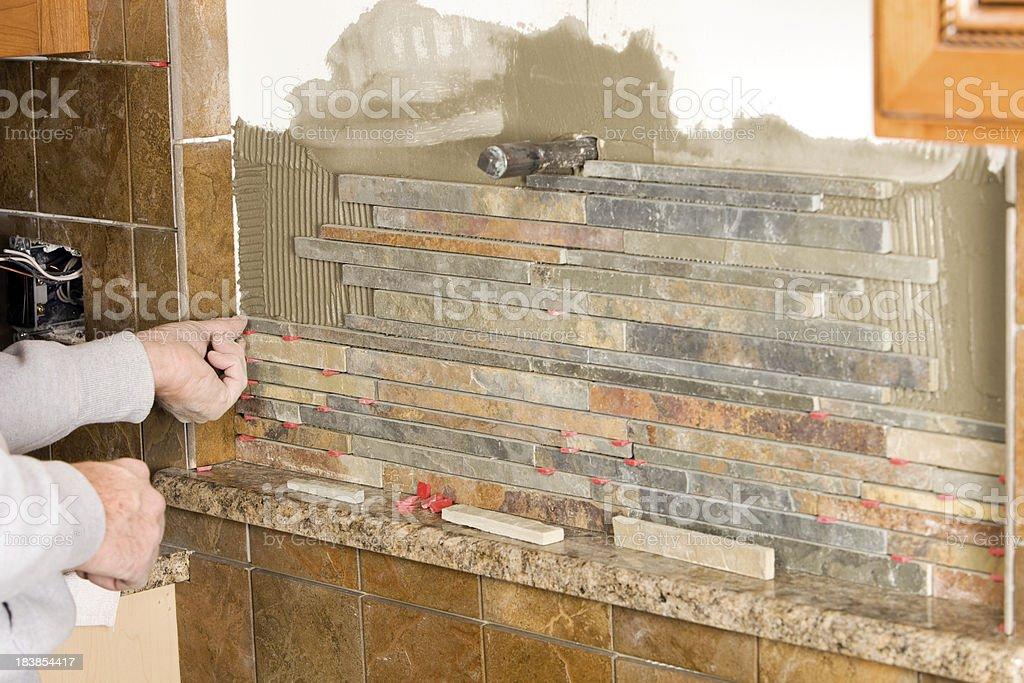 Worker Installing a Stacked Stone Tile Backsplash stock photo