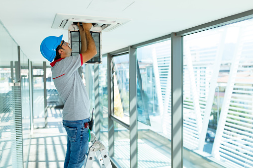 Worker installing air conditioner in building