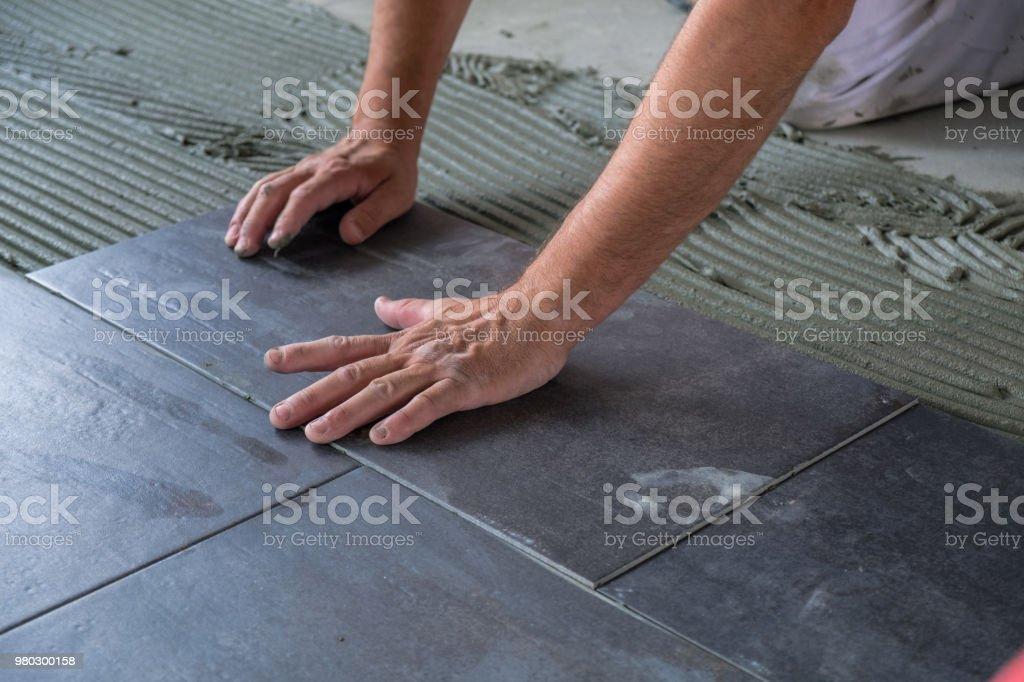 Worker installing ceramic floor tiles royalty-free stock photo