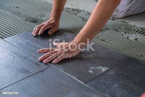 istock Worker installing ceramic floor tiles 980300158