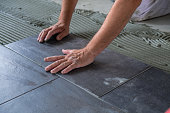 Worker's hands pressing ceramic floor tiles laid on applied adhesive