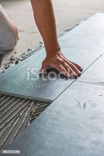 istock Worker installing ceramic floor tiles 980300288