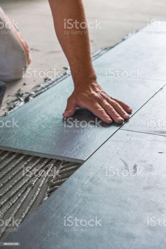 Worker installing ceramic floor tiles stock photo