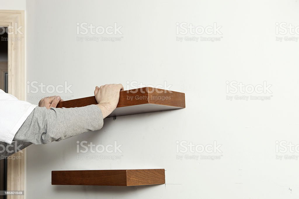 Worker Installing Cherry Wall Shelf at Remodeling Project royalty-free stock photo