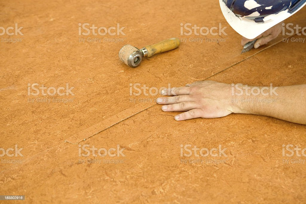 Worker Installing Commercial Grade Linoleum Flooring - Stock image .