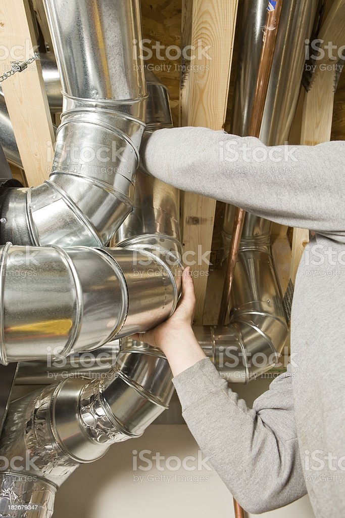 HVAC worker installing ducts for air exchanger stock photo
