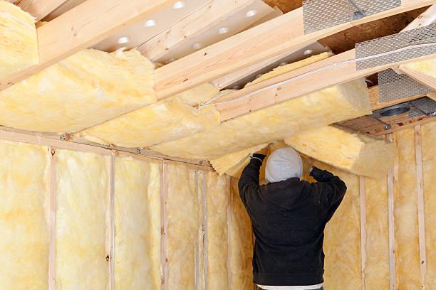 Worker Installing Fiberglass Batt Insulation between Roof Trusses stock photo