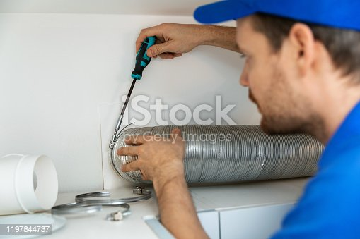 895571294 istock photo worker installing flexible aluminum ventilation tube for kitchen cooker hood exhaust system 1197844737