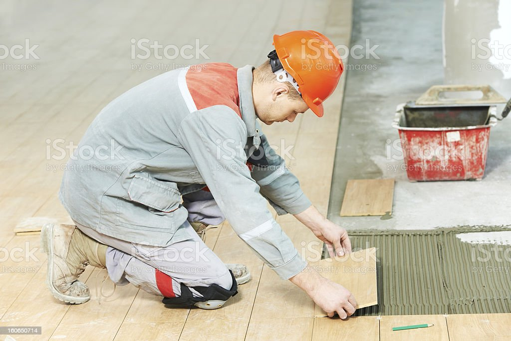 Worker installing floor tile at construction site stock photo