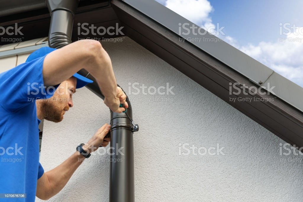 worker installing house roof gutter stock photo