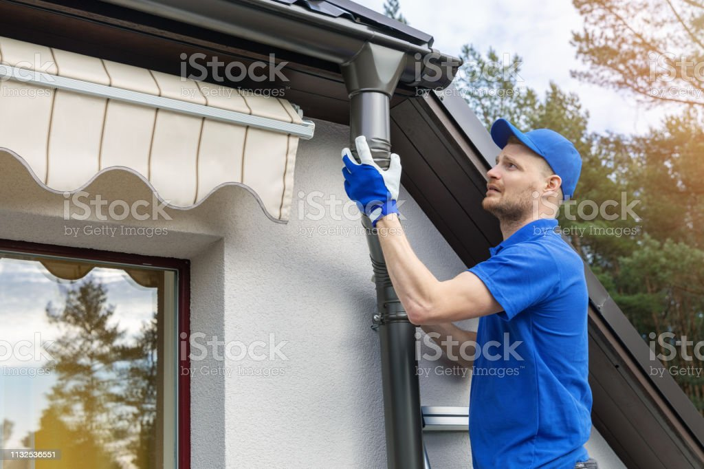 worker installing house roof rain gutter system stock photo