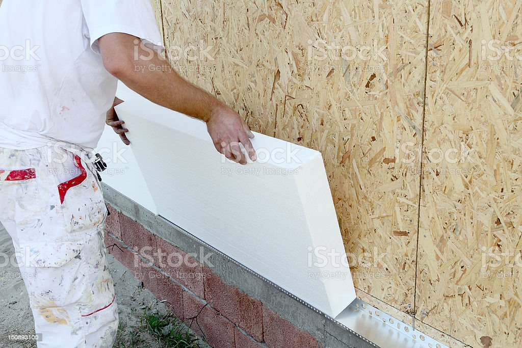 Worker installing insulation board stock photo