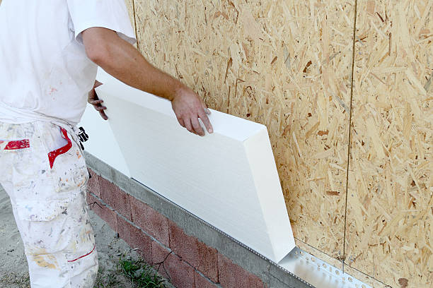 Worker installing insulation board Worker placing styrofoam sheet insulation to the wall polystyrene stock pictures, royalty-free photos & images