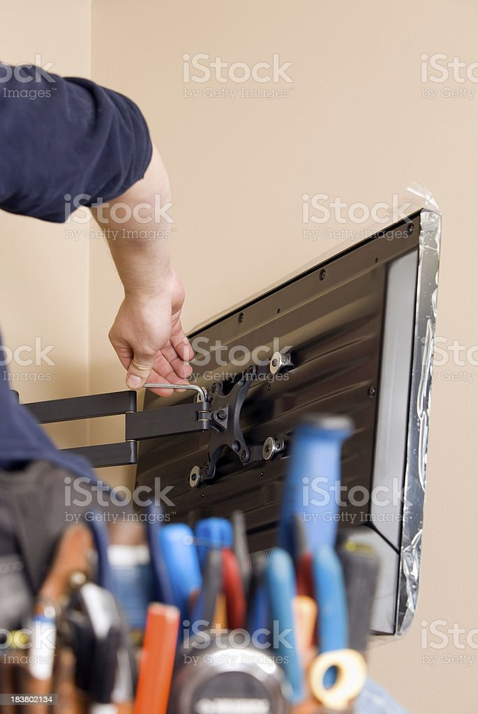 Worker Installing New TV with Tool Belt Foreground royalty-free stock photo
