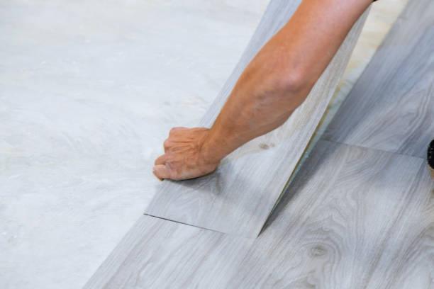 arbeiter installiert neue vinyl-fliesenboden laminat holz textur boden mit neuen hausverbesserung - pvc stock-fotos und bilder