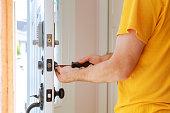 istock Worker installing or repairing new lock 1093238062
