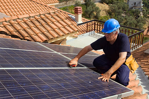 Worker installing photovoltaic panels on rooftop stock photo