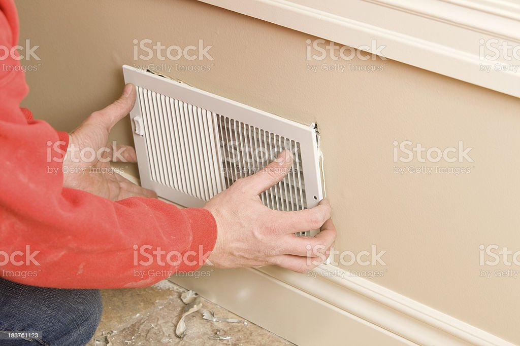 HVAC Worker Installing Residential Room Vent royalty-free stock photo