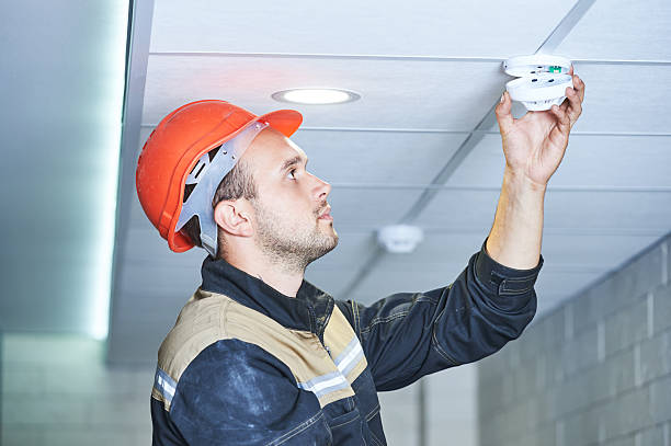 worker installing smoke detector on the ceiling – Foto