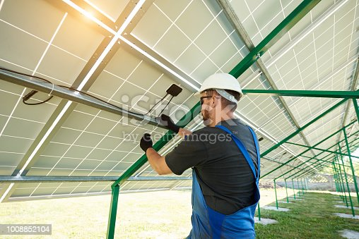 istock Worker installing solar panels during sunny day 1008852104