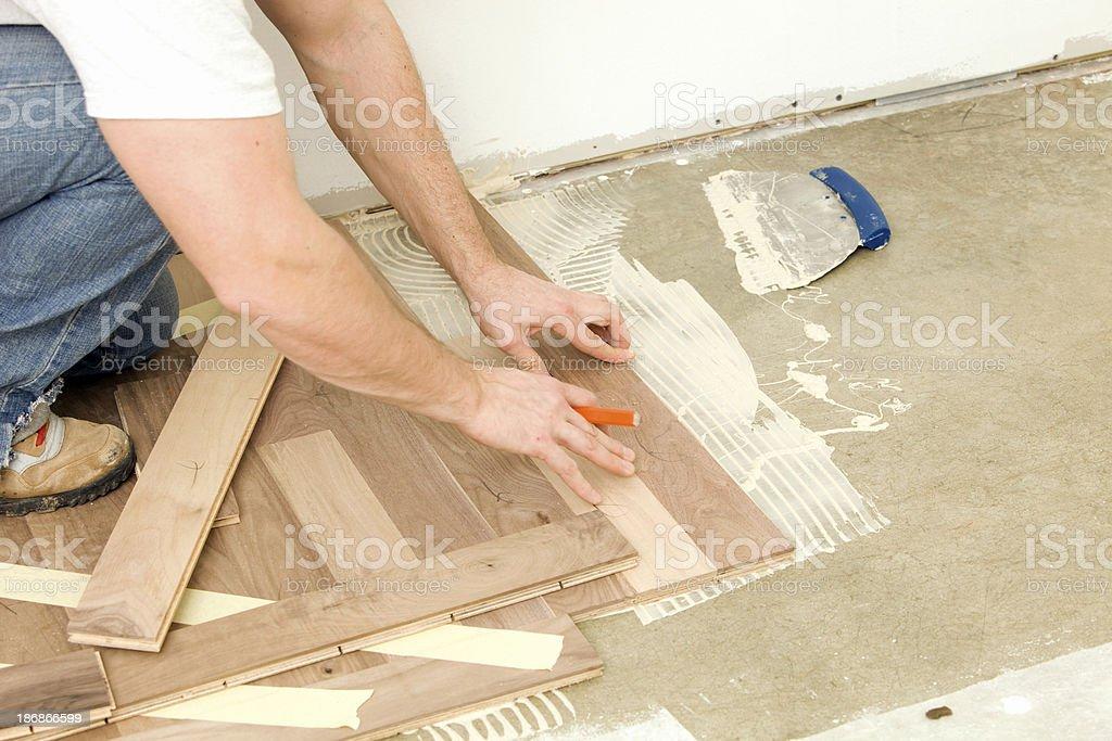 Worker Installing Walnut Hardwood Floor over Concrete royalty-free stock photo