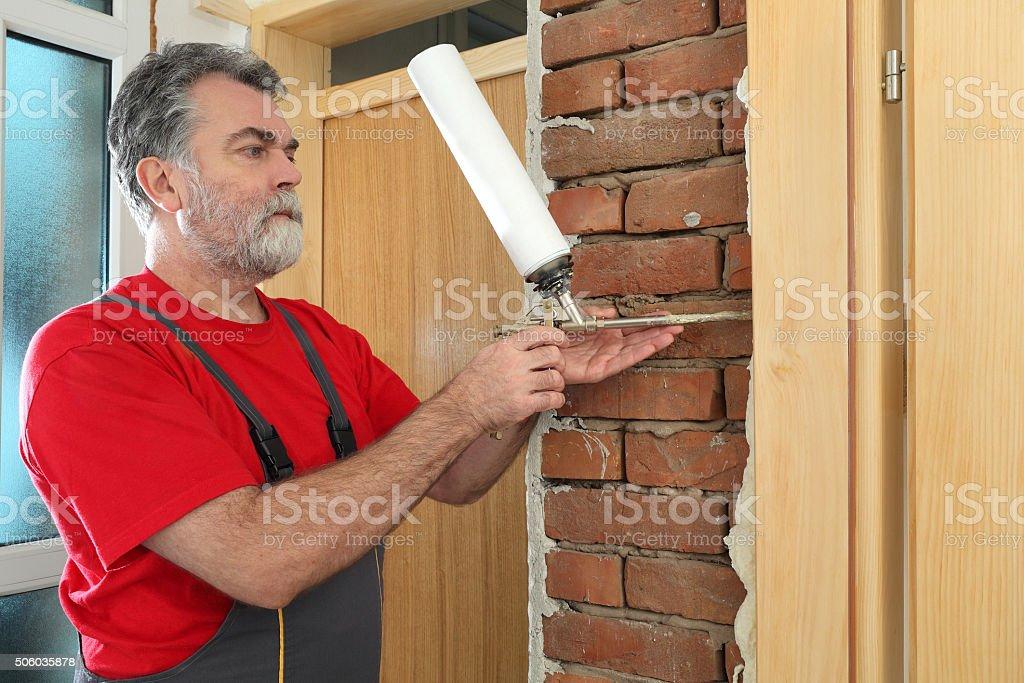 Worker installing wooden door, using polyurethane foam stock photo