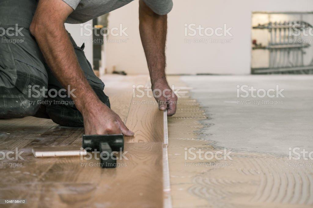 Worker installing wooden flooring stock photo
